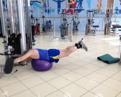 Тяга двух ног с верхнего блока — исходное (фитбол), на развитие нижней части спины